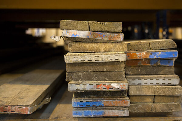A stack of scaffold boards. Image shows the ends of the boards with metal fixings on display.